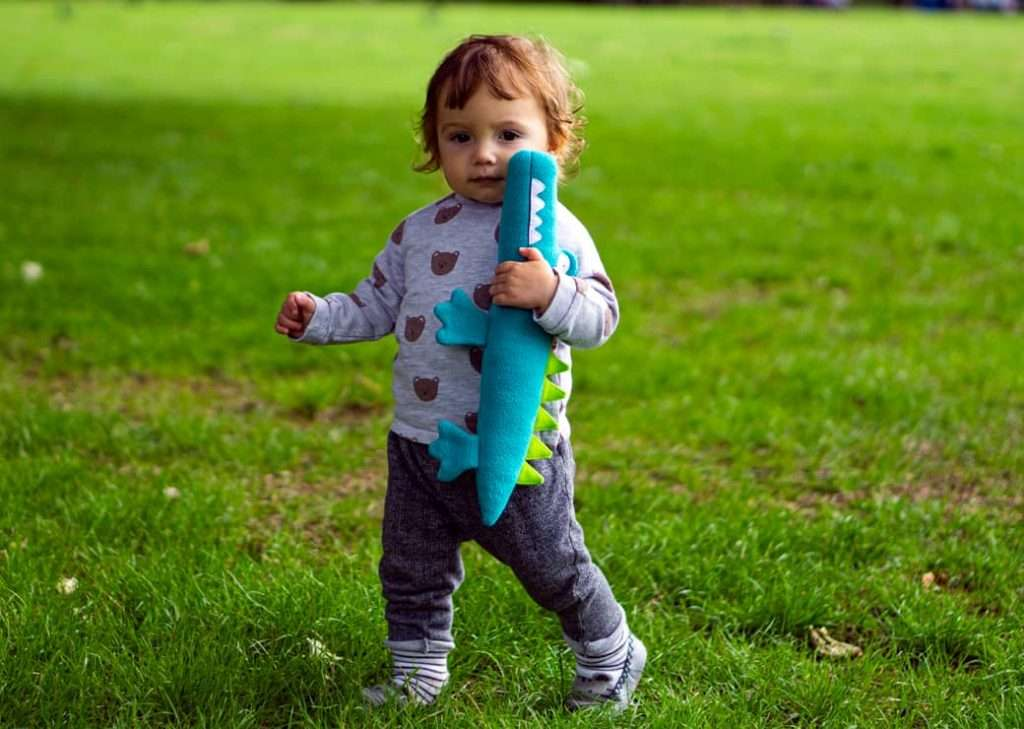 baby playing stuffed crocodile toy