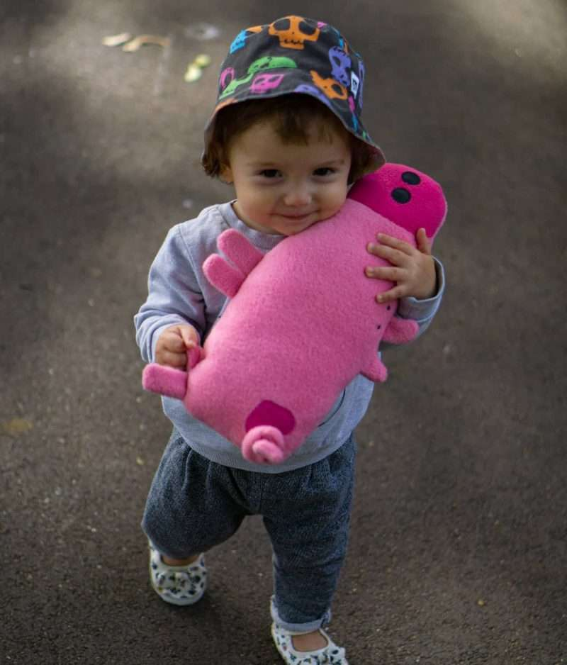 Happy baby playing with stuffed pink pig toy