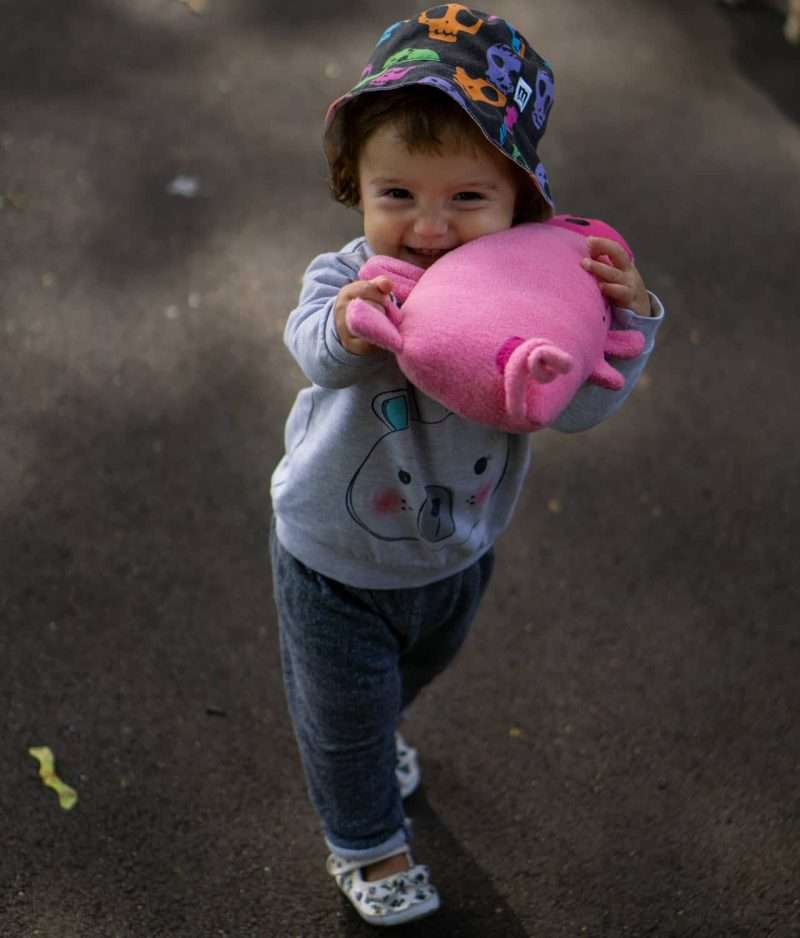 Happy baby playing with stuffed pig toy