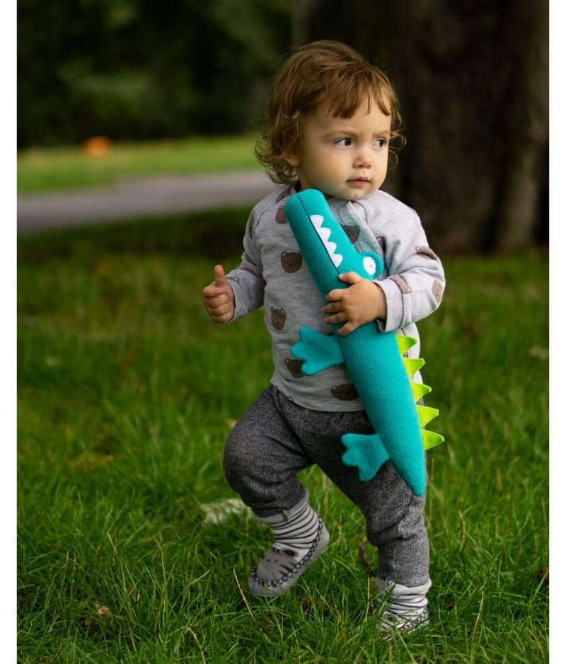 Small baby playing with stuffed alligator toy
