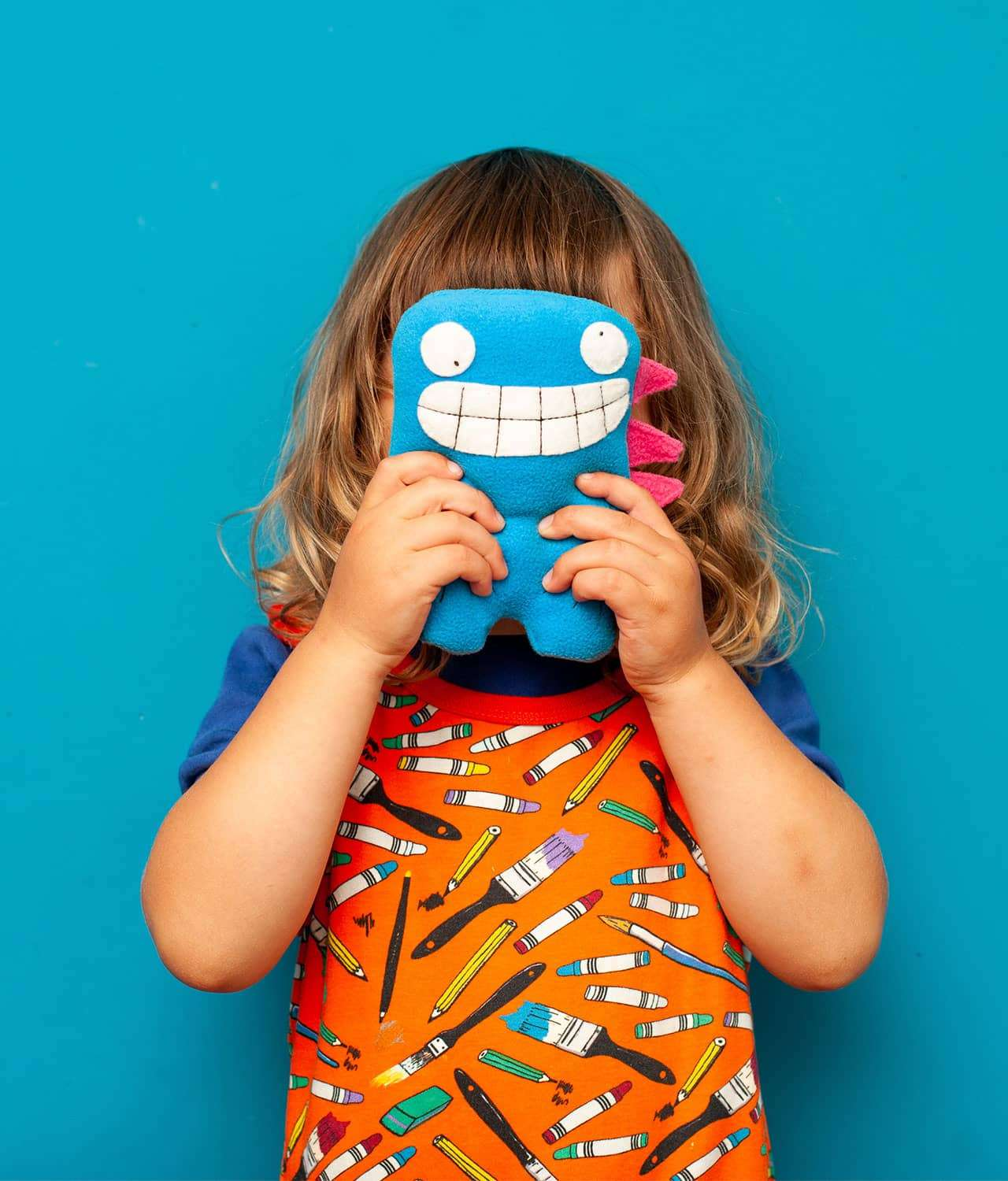 Kid playing with stuffed monster toy