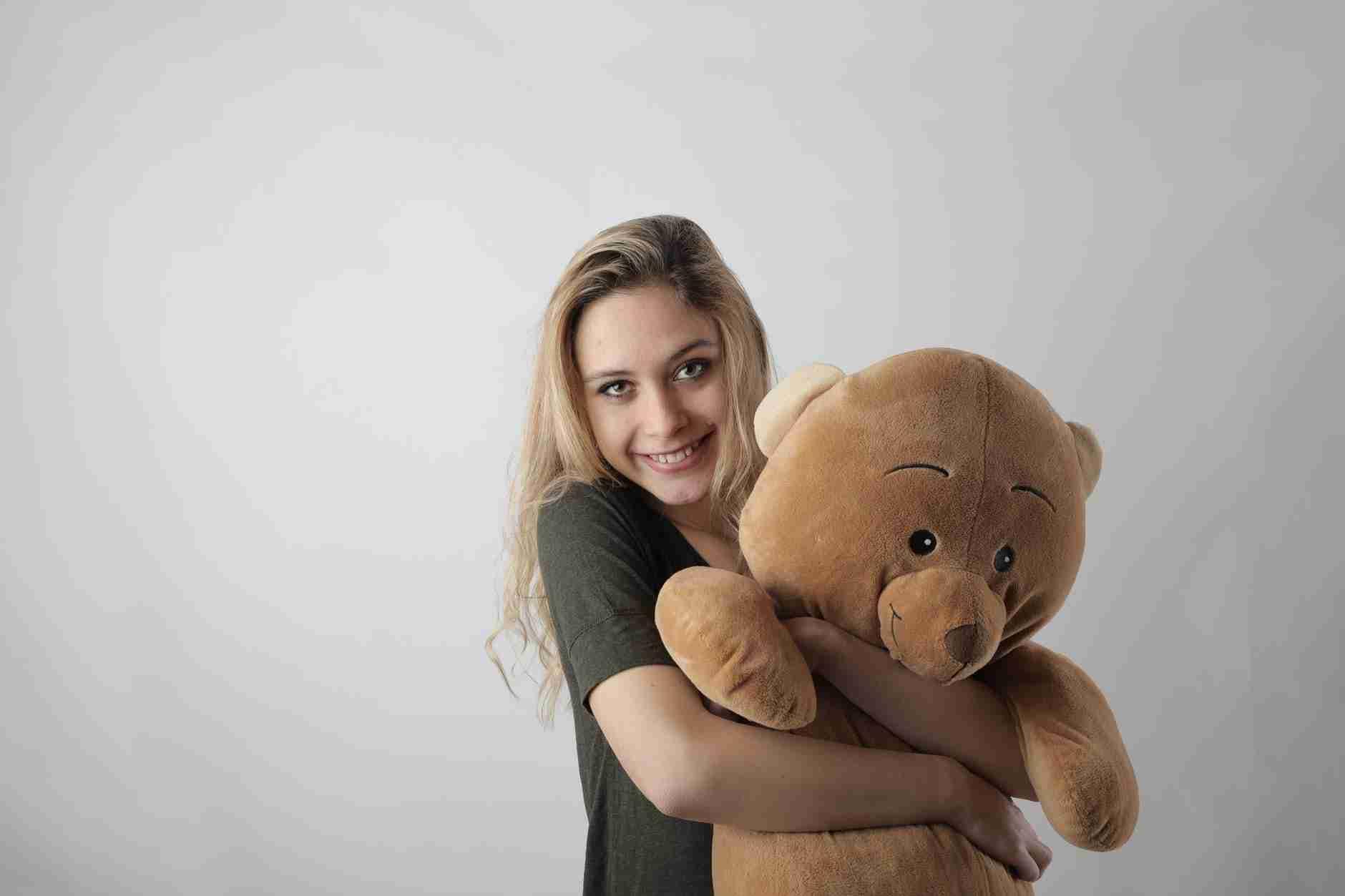 woman hugging a bear stuff toy